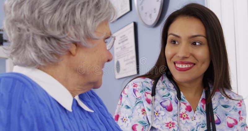 Verzorger en hogere patiënt die samen spreken royalty-vrije stock fotografie