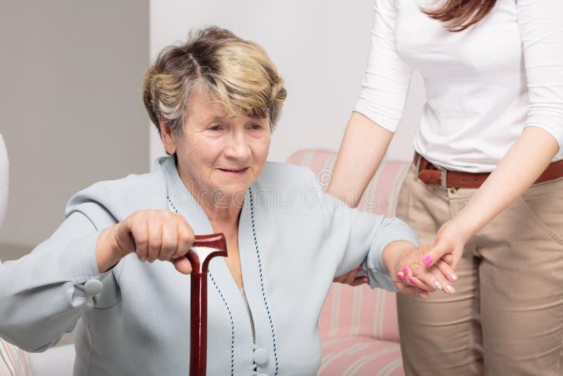 Verzorger ondersteunend hogere vrouw met wandelstok stock foto's