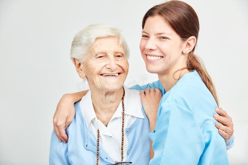 Verzorgingshulp en gelukkige hogere vrouw die elkaar koesteren stock foto's