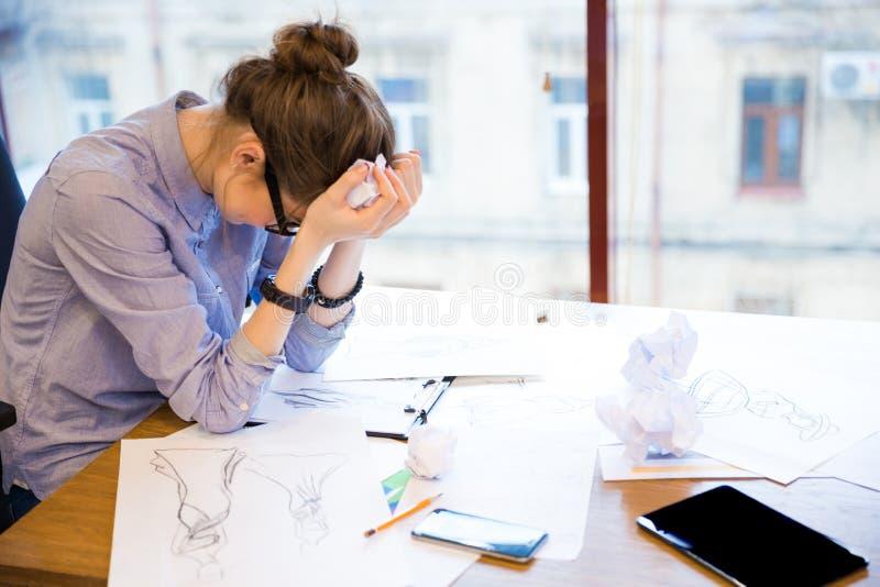 Verzweifelter Frauenmodedesigner, der im Büro mit Skizzen sitzt lizenzfreie stockfotos
