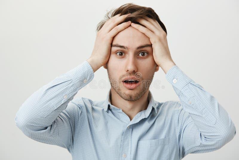 Verzweiflungs- und Bedauernkonzept Porträt des entsetzten attraktiven jungen Geschäftsmannhändchenhaltens auf Stirn, schauend mit lizenzfreie stockbilder