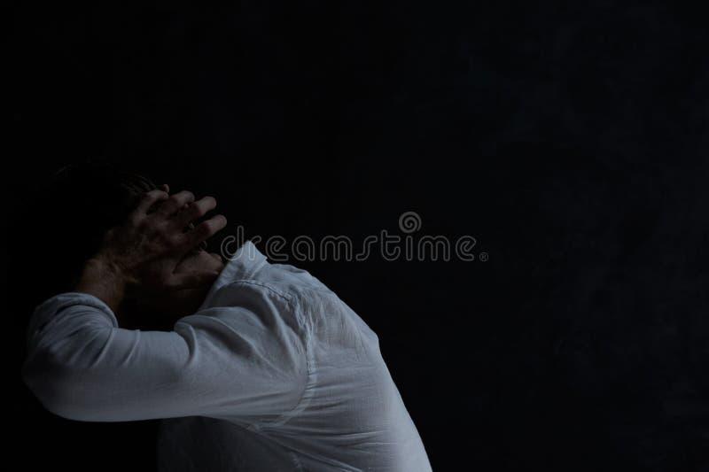 Verzweiflungsmann in der Dunkelkammer lizenzfreie stockbilder