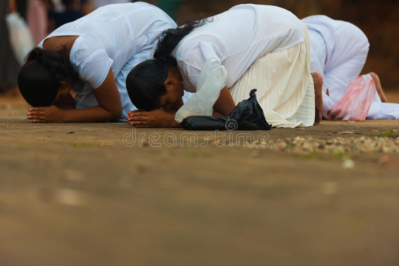 Vesak Full Moon Poya Day Sri Lanka Women Praying. UNAWATUNA, SRI LANKA - MAY 19, 2008: Sinhalese buddhist women at a local temple bow low in prayer on Vesak Full stock images