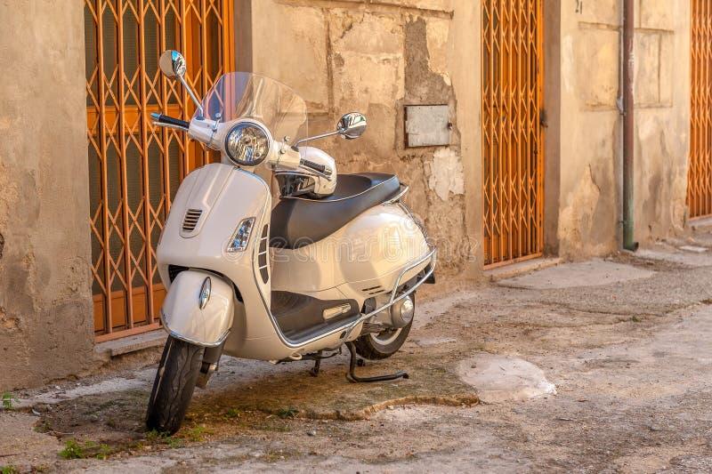 Vespa blanc sur une petite rue laide dans la vieille ville, Italie image stock