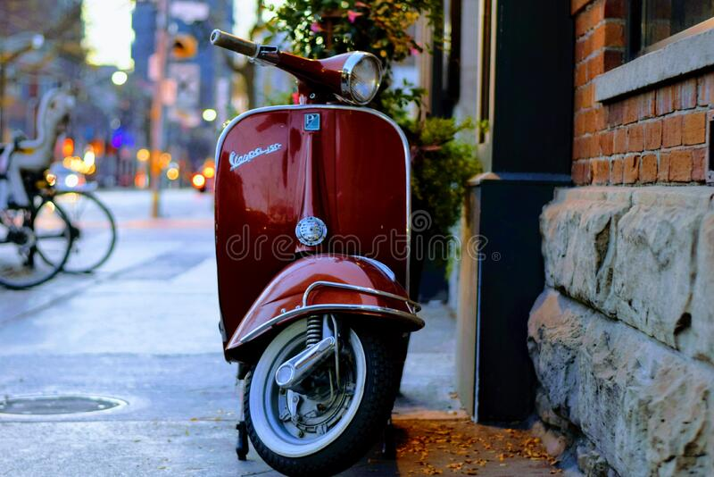 Vespa on city sidewalk royalty free stock images