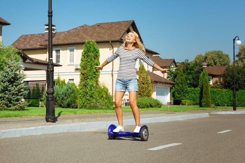 Vespa de uno mismo-equilibrio del montar a caballo feliz de la mujer abajo de la calle foto de archivo libre de regalías