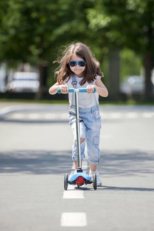 Vespa del montar a caballo del niño Niño en tablero colorido del retroceso Diversión al aire libre activa para los niños Deportes foto de archivo