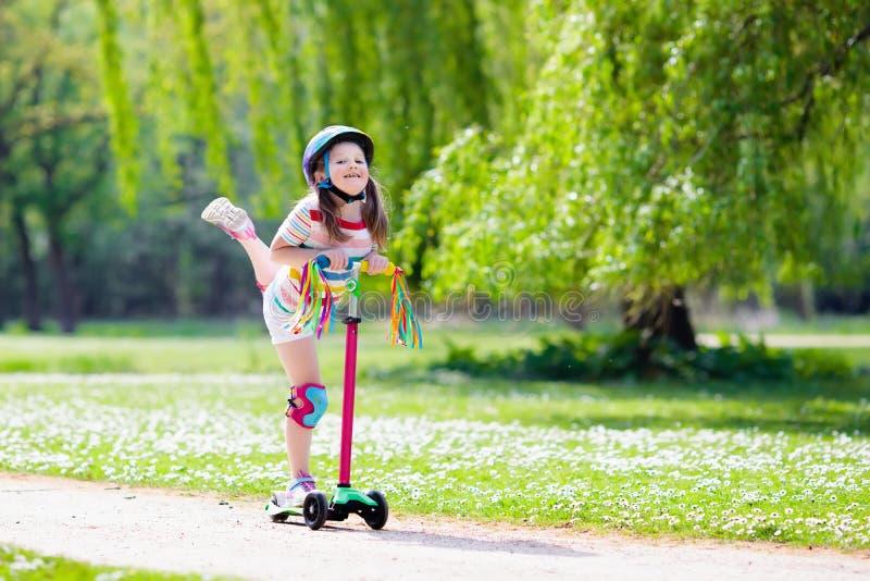 Vespa del retroceso del montar a caballo del niño en parque del verano foto de archivo
