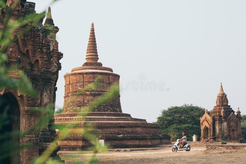 Vespa eléctrica del montar a caballo del hombre hacia los templos y las pagodas de Bagan antiguo en Myanmar imagenes de archivo