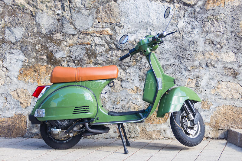 Scooter. Green vespa parked against a granite wall - Side view. Also known as Vespa or Lambretta stock photography