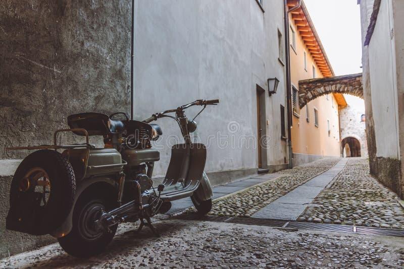 Vespa gris vieja parqueada en un callejón estrecho en Ascona imagen de archivo libre de regalías