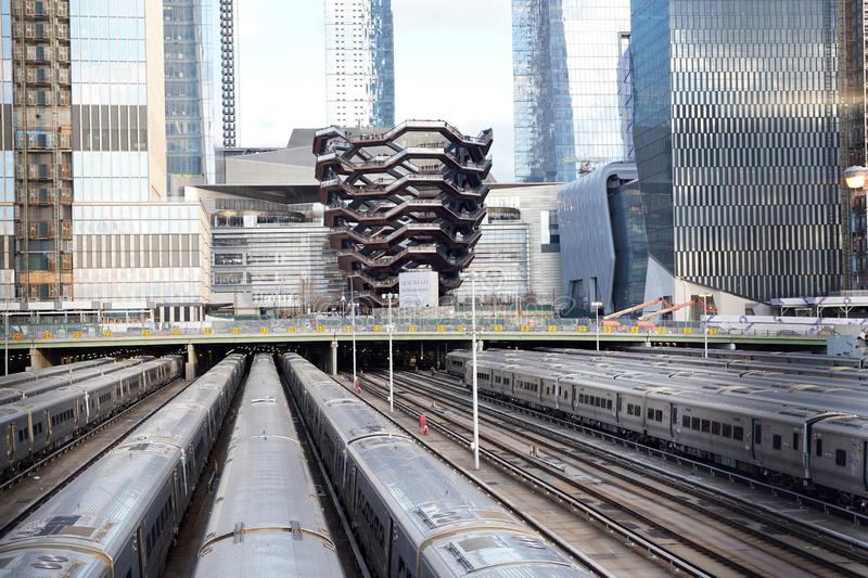 Vessel  TKA, a spiral staircase, with railroad and trains in front, skycrappers behind,  Hudson Yards, Manhattan`s West Side, NY royalty free stock photos