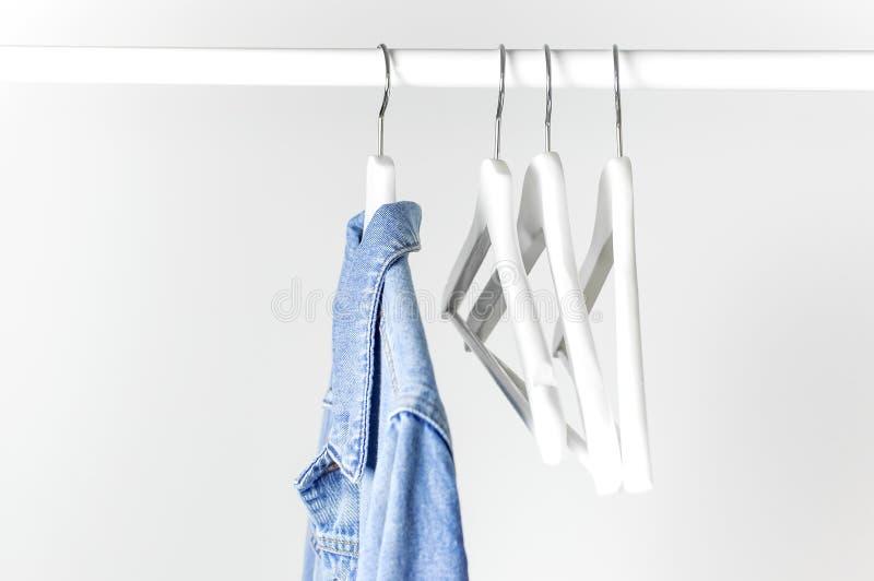 Veste bleue de denim sur le cintre de manteau en bois blanc sur une tige contre l'espace ?tendu plat de copie de mur gris-clair D photos libres de droits
