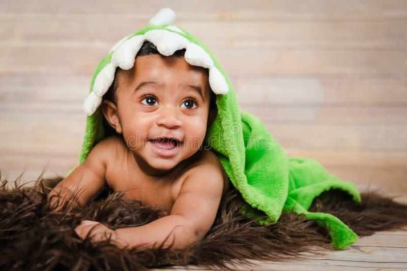 Veste de banho vestindo do menino infantil do dogla que coloca em seu do tiro moderno de madeira peludo macio do estúdio do fundo fotos de stock