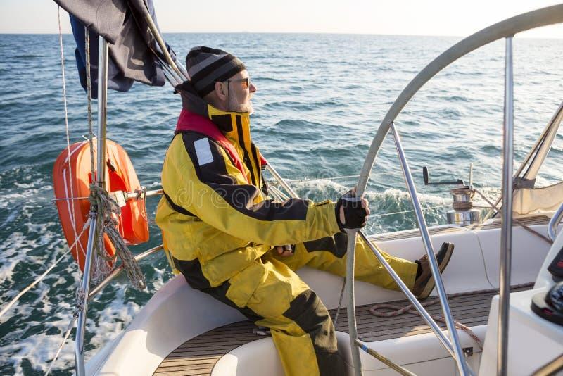Veste de port de vent d'homme mûr sur le bateau à voile photos libres de droits
