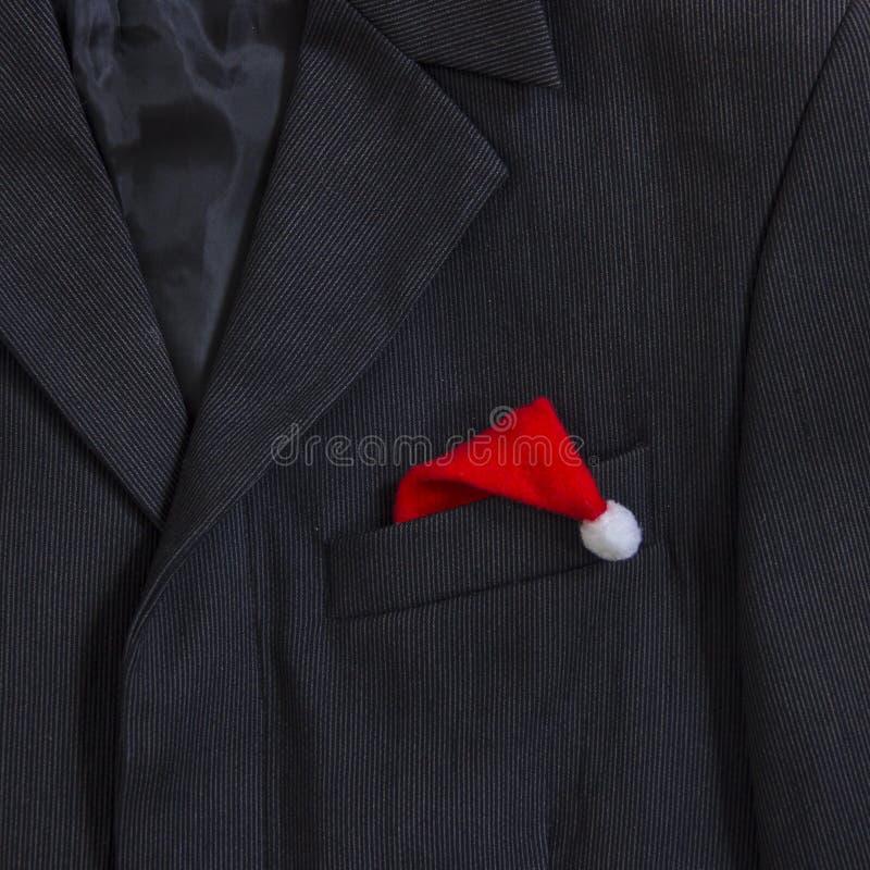 Veste foncée du ` s d'hommes dans la petite douille de poche de collier de rayures dans la place de chapeau de Santa Claus de cha images stock