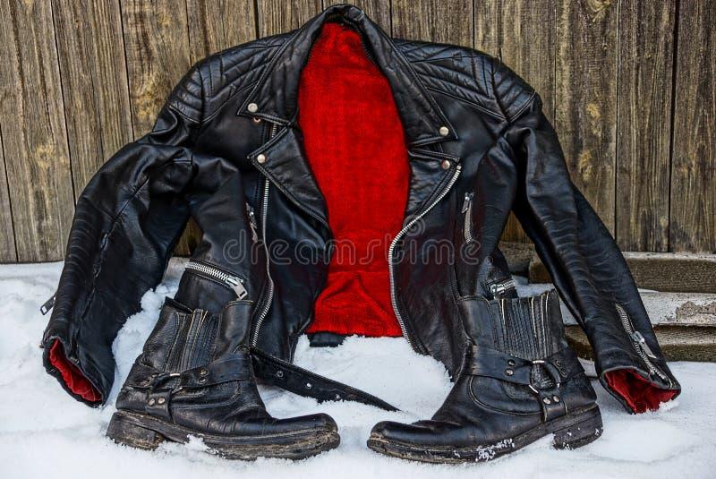 Veste noire avec une doublure rouge et bottes dans la neige photo stock
