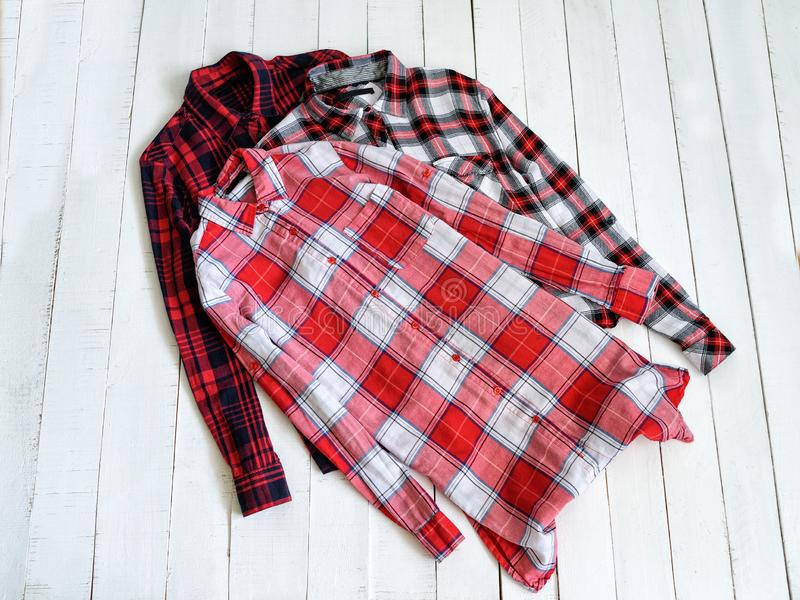 Veste o conceito Três camisas quadriculados em um fundo de madeira Vista superior fotografia de stock royalty free