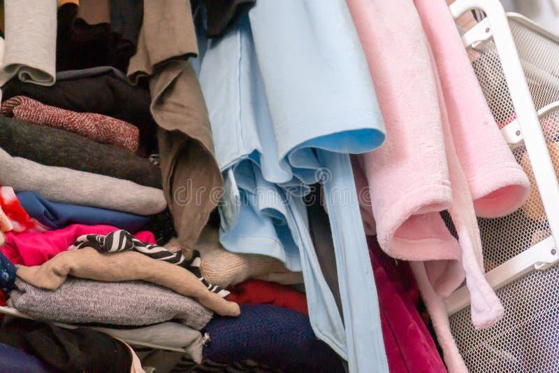 Vestes azuis e cor-de-rosa da casa que penduram acima do armário dobrado, empilhado e desarrumado da mulher, com necessidade da  foto de stock