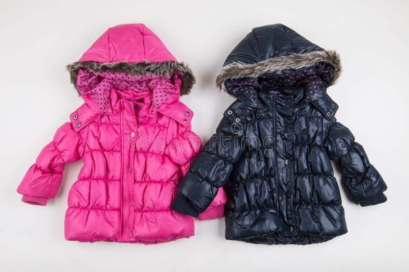 Vestes bleues et roses mignonnes d'hiver du ` s d'enfants images stock