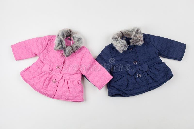 Vestes de l'hiver des enfants roses et bleus pour la fille et le garçon image libre de droits
