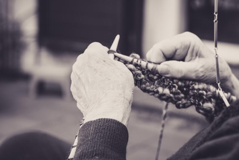 vestida nas mãos da velha senhora para tricô fotos de stock