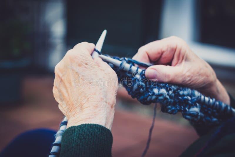 vestida nas mãos da velha senhora para tricô imagens de stock royalty free