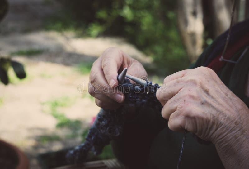 vestida nas mãos da velha senhora para tricô foto de stock royalty free