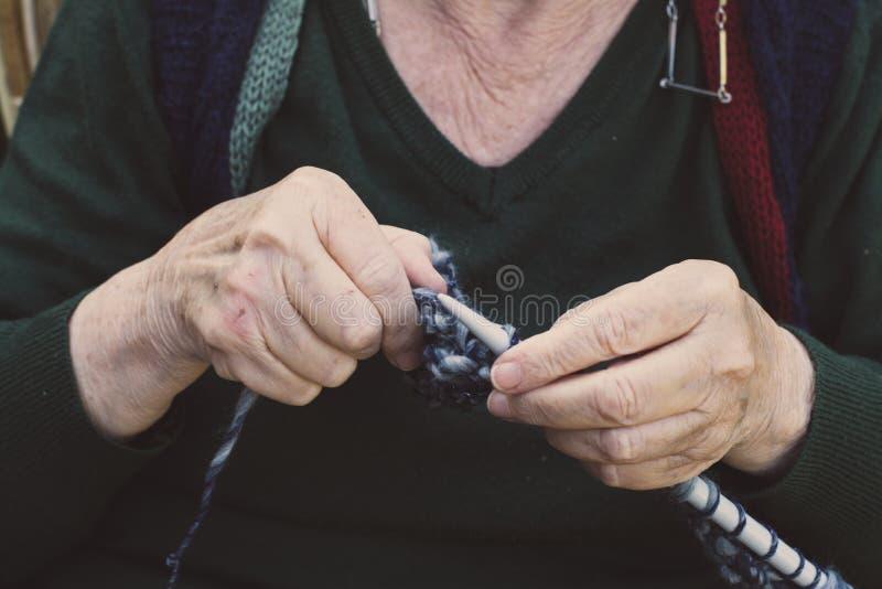 vestida nas mãos da velha senhora para tricô fotografia de stock
