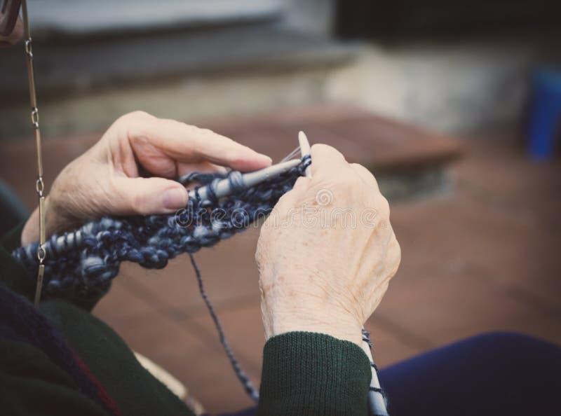 vestida nas mãos da velha senhora para tricô foto de stock