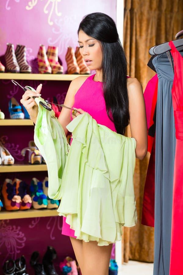 Vestido asiático da compra da mulher na loja da forma fotos de stock