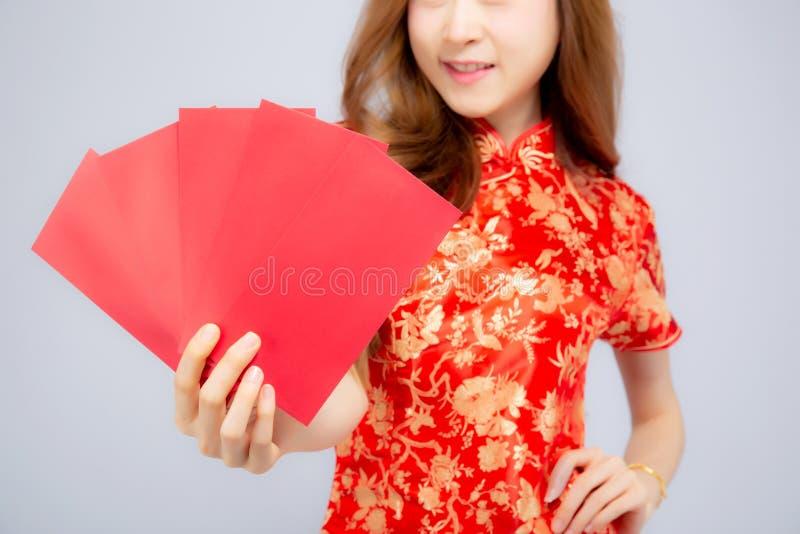 Vestido asiático joven del cheongsam de la mujer del retrato hermoso del primer que sonríe sosteniendo el sobre rojo en el fondo  fotos de archivo