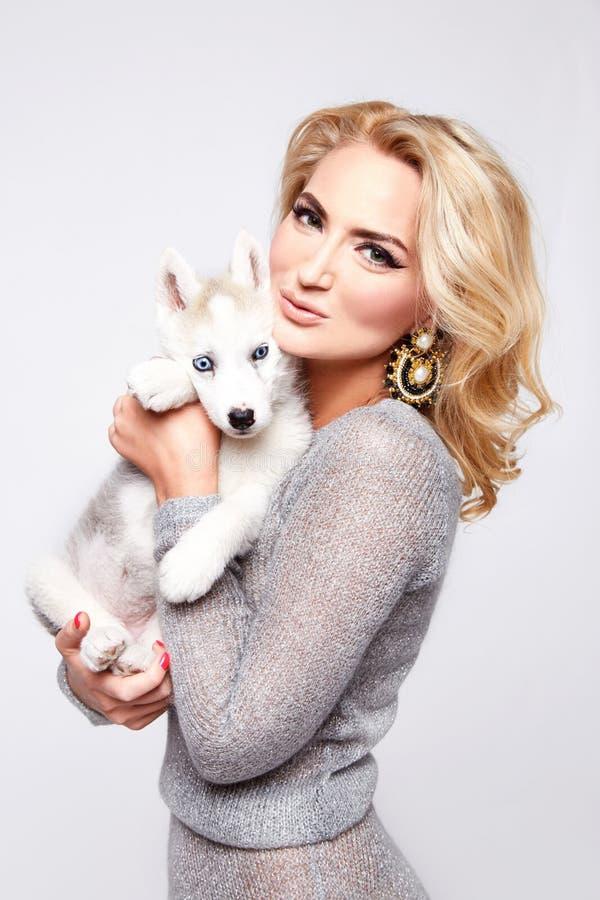 Vestido atractivo hermoso del maquillaje del perro de animales domésticos del abrazo de la mujer rubio fotografía de archivo