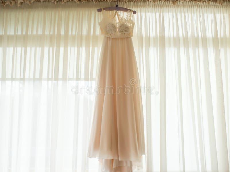 Vestido beige hermoso de la gasa que cuelga en la suspensión foto de archivo libre de regalías
