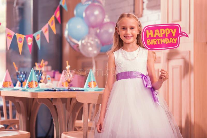 Vestido blanco que lleva de la muchacha linda y llevar a cabo la muestra del feliz cumpleaños imagen de archivo