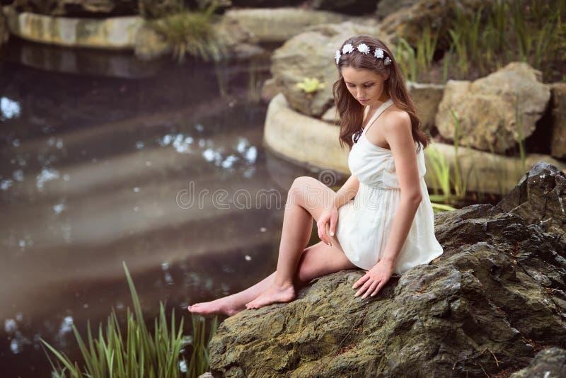 Vestido blanco que lleva de la mujer hermosa que se sienta en la roca cerca de un lago imagen de archivo