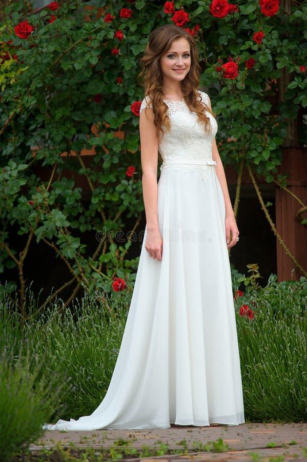 Vestido blanco que lleva hermoso sonriente de la mujer joven que presenta cerca del bl foto de archivo