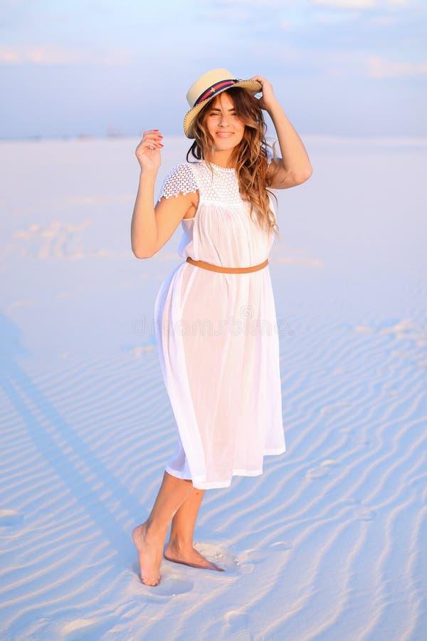 Vestido blanco que lleva joven y sombrero de la persona femenina que se colocan en la arena fotografía de archivo libre de regalías