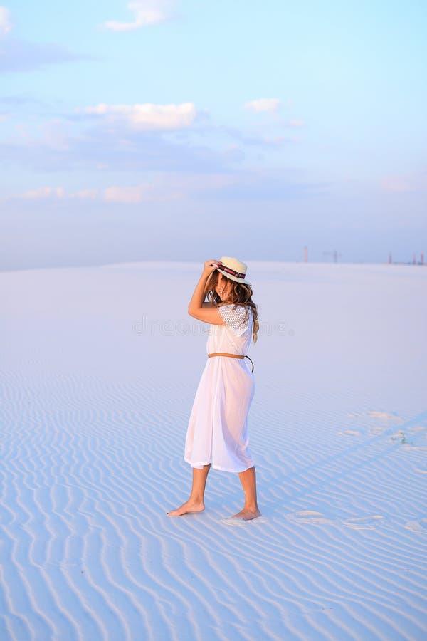 Vestido blanco que lleva y sombrero de la mujer bonita joven que caminan en la arena i imágenes de archivo libres de regalías