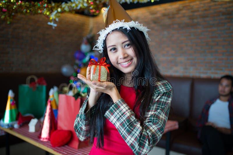 Vestido bonito do desgaste de mulher e chapéu vermelhos de Papai Noel que mostra a caixa de presente dourada disponível no restau imagens de stock royalty free