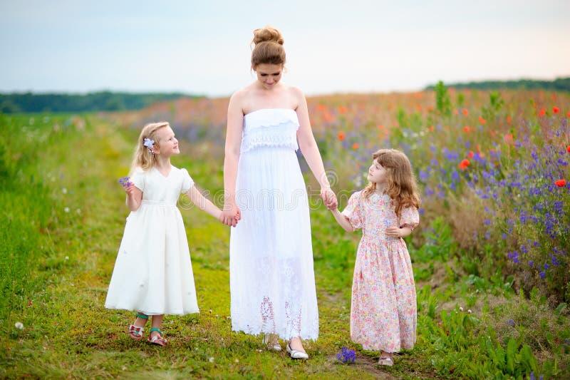 Vestido branco vestindo da mãe bonita com passeio de duas meninas imagens de stock