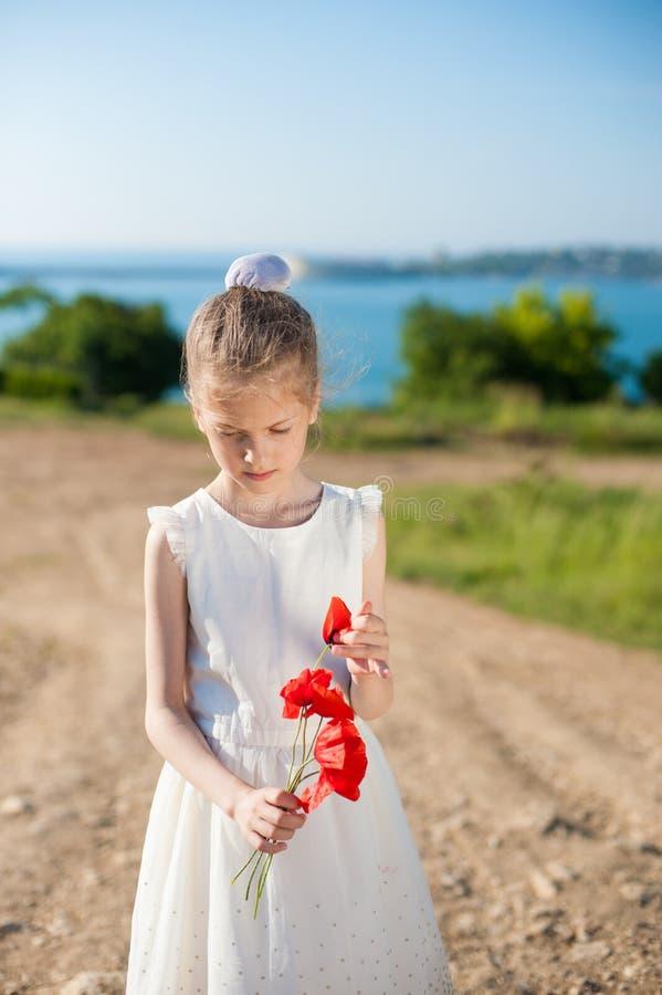 Vestido branco vestindo da menina pensativa com um ramalhete de papoilas vermelhas fora na mola imagem de stock