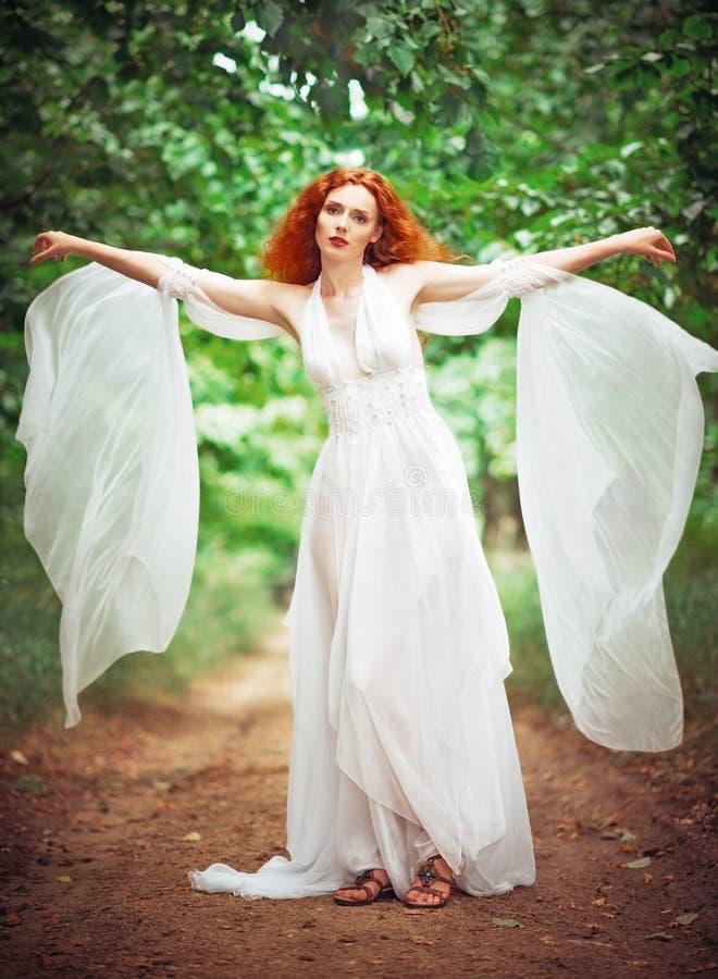 Vestido branco vestindo da mulher bonita do ruivo em um jardim imagem de stock