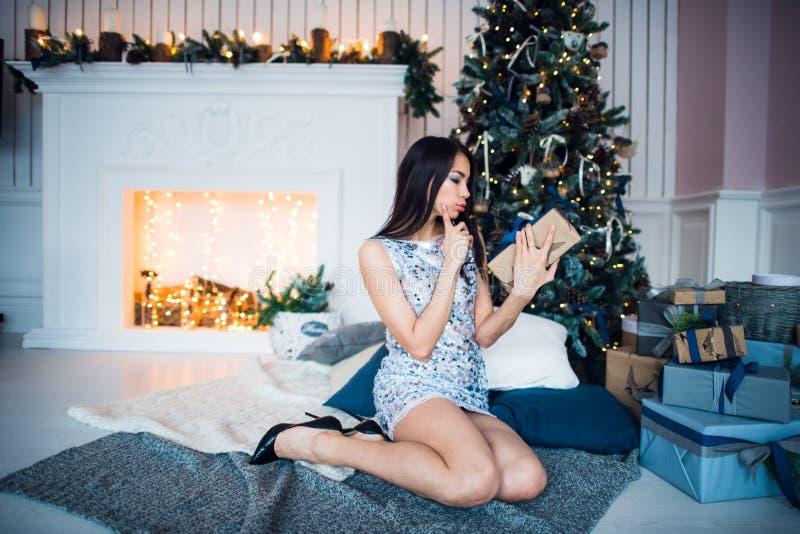 Vestido brilhante surpreendente vestindo da mulher com um presente do Natal no fundo interior do Natal com uma árvore de abeto e foto de stock