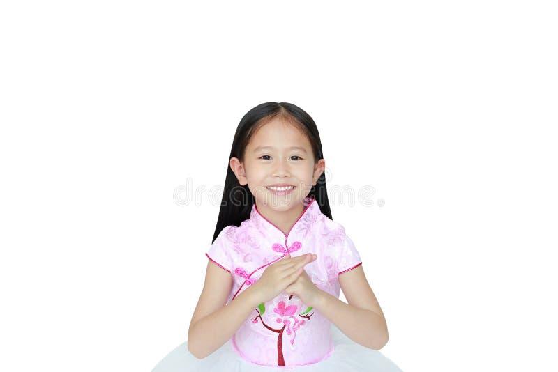 Vestido chinês tradicional vestindo do rosa da menina asiática pequena feliz da criança com celebração do gesto do cumprimento pe fotos de stock royalty free