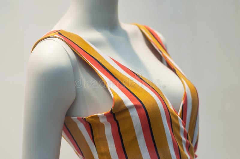 vestido colorido del verano en maniquí en la sala de exposición de la tienda de la moda de las mujeres foto de archivo