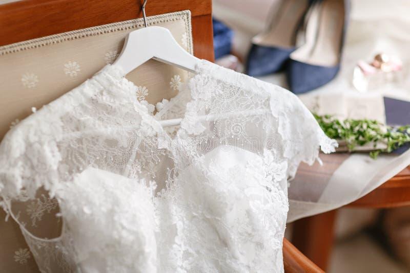 Vestido de boda blanco con el cordón que miente en la silla diversas flores del ramo Manojo nupcial moderno con la flor de la ama foto de archivo