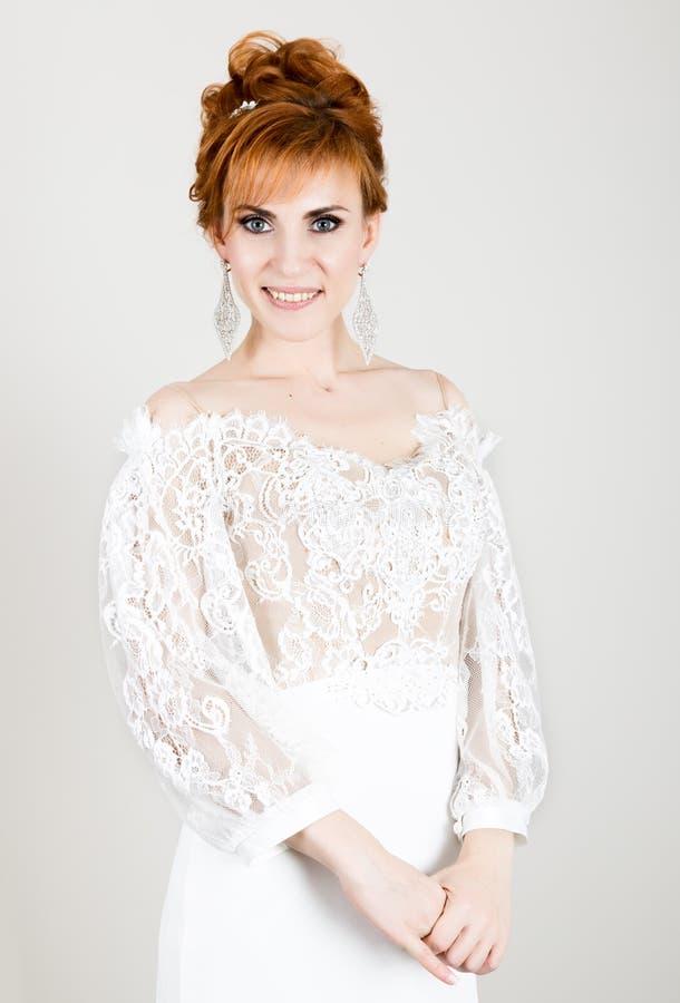 Vestido de boda blanco de la novia joven hermosa del pelirrojo que lleva con maquillaje y el peinado profesionales imagen de archivo