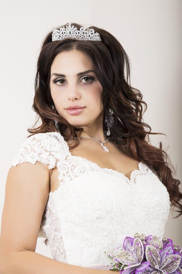Vestido de boda blanco de la novia que lleva joven hermosa con maquillaje profesional foto de archivo libre de regalías