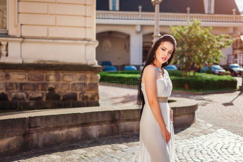 Vestido de boda blanco de la mujer que lleva hermosa al aire libre en ciudad vieja Vestido con los accesorios y la joyería fotografía de archivo